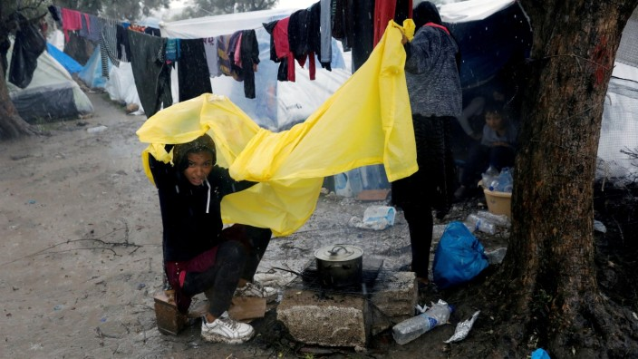A girl tries to protect herself from the rain at a makeshift camp for refugees and migrants next to the Moria camp during a rainfall, on the island of Lesbos