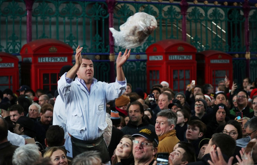 A butcher throws a cut of meat to a customer during a Christmas Eve auction in Smithfield market in London