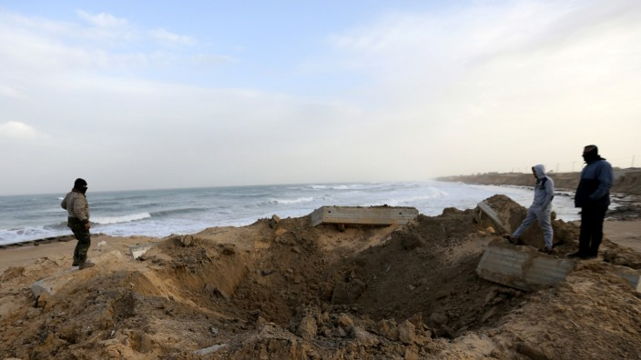 Palestinians check the site of an Israeli air strike in the southern Gaza Strip