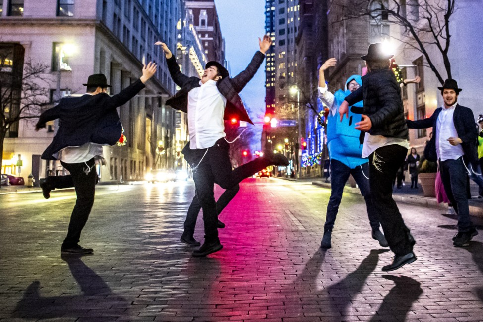 Yeshiva School students briefly dance on Grant Street after the menorah lighting outside of the City-County Building for the fifth night of Hanukkah, Thursday, Dec. 26, 2019, in downtown Pittsburgh.  (Alexandra Wimley/Pittsburgh Post-Gazette via AP)