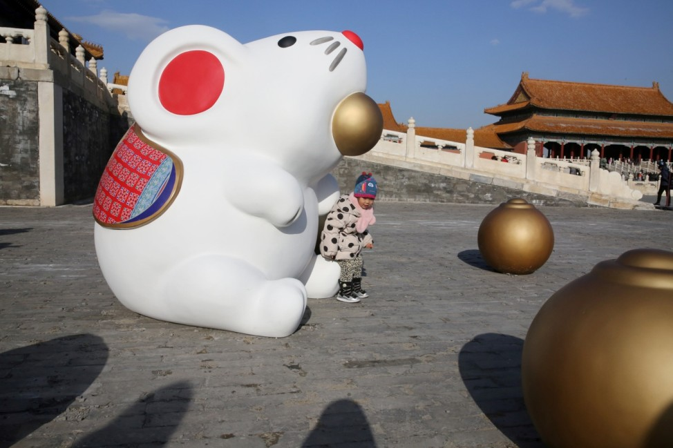 Child sits on an installation of a rat, the Chinese zodiac sign for the next Lunar New Year, at the Forbidden City in Beijing