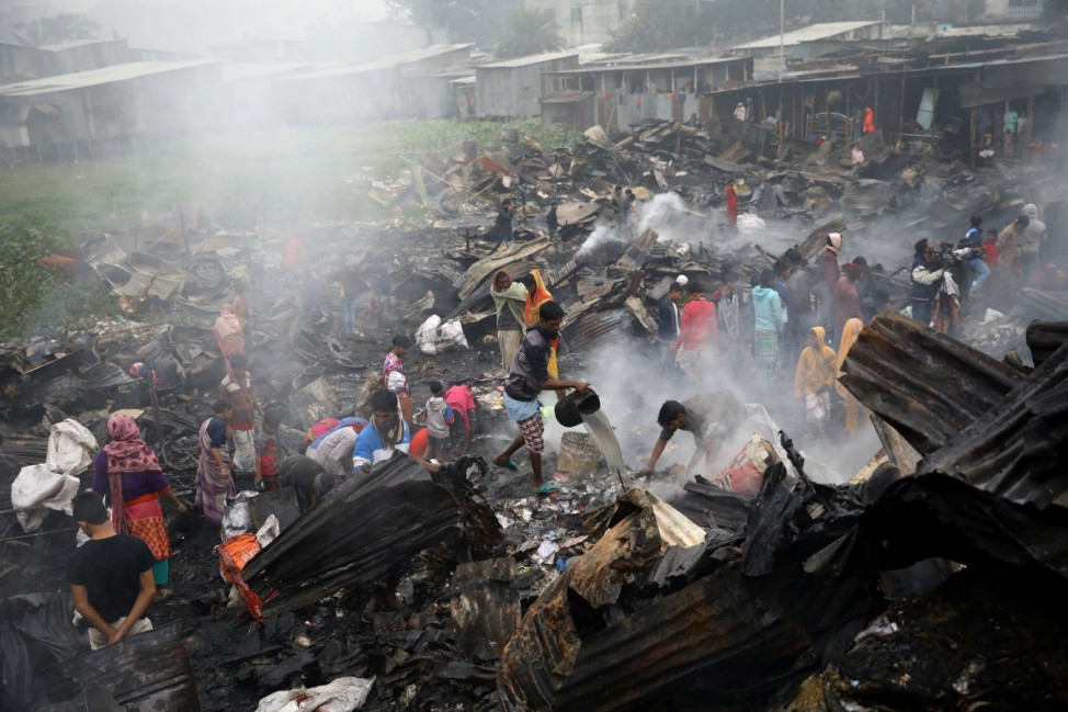 Slum dwellers collect leftovers from ashes, whose shelter has been burned after a fire broke out in a slum in Dhaka