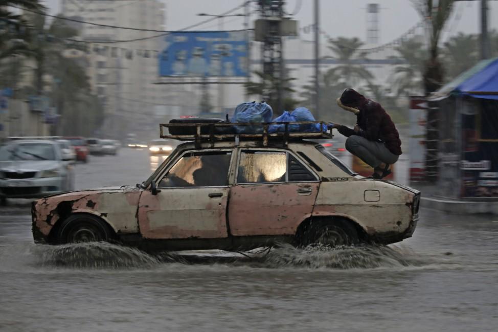 Blinder Passagier: In Gaza fährt ein Auto nach einem Starkregen durch die überfluteten Straßen.