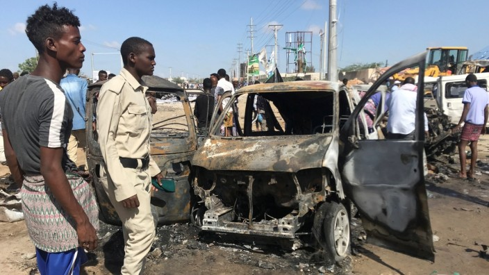Somali security assess the scene of a car bomb explosion at a checkpoint in Mogadishu