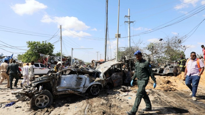 FILE PHOTO: A Somali police officer walks past a wreckage at the scene of a car bomb explosion at a checkpoint in Mogadishu