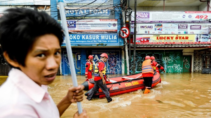 Members of a rescue team prepare an inflatable boat to evacuate locals as floods hit the Jatinegara area after heavy rains in Jakarta