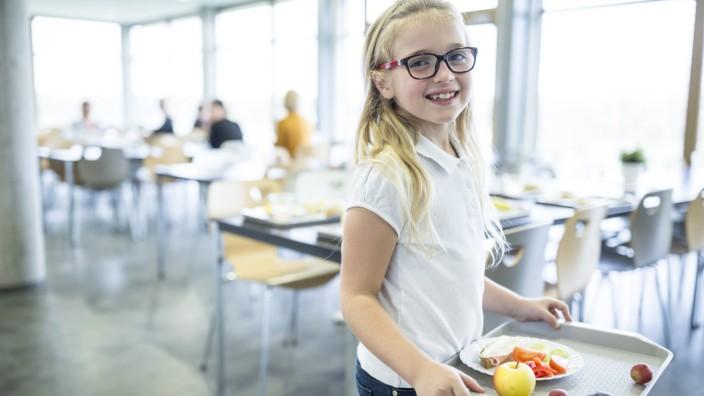 Portrait of smiling schoolgirl carrying tray in school canteen model released Symbolfoto property re
