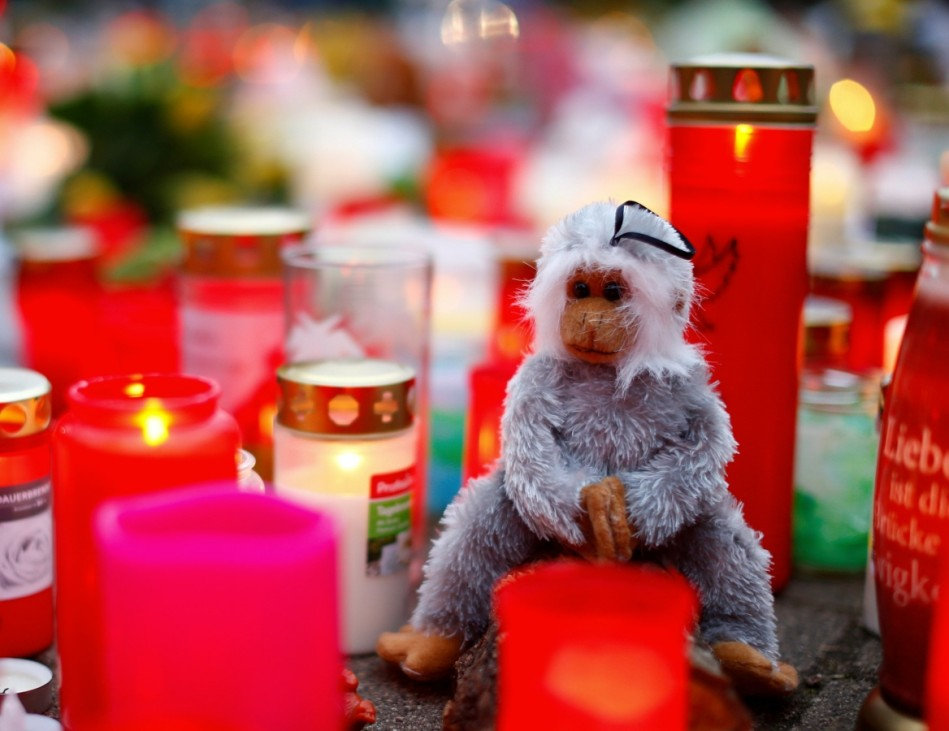A toy monkey is seen between flowers and candles outside the zoo of Krefeld