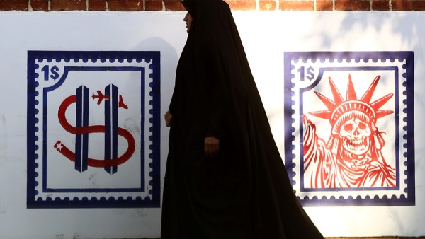 A woman walks past an Anti US mural on the former US embassy's wall in Tehran