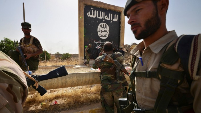 Shi'ite Popular Mobilization Forces (PMF) sit next to the black flag sign commonly used by Islamic State militants, after liberating the city Hawija