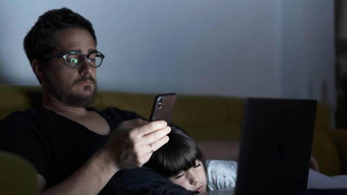 Father using laptop and cell phone on couch at night with daughter sleeping model released Symbolfot