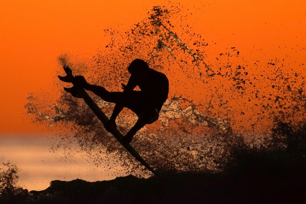 A surfer takes some air off a wave while surfing after sunset in Cardiff, California