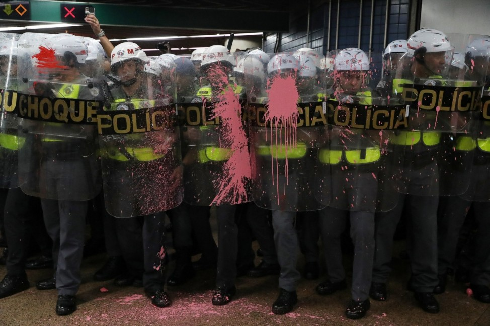 Riot police officers are seen with their shields with paint thrown by demonstrators, who are prevented from jumping over turnstiles, after a protest against fare hikes for city buses in Sao Paulo