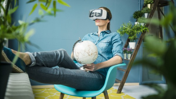 Beautiful woman sitting in her home decorated with plants holding globe wearing VR glasses model