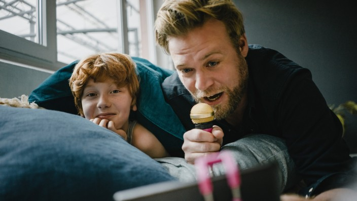 Father and son with smartphone and microphone at home model released Symbolfoto property released PUBLICATIONxINxGERxSUI