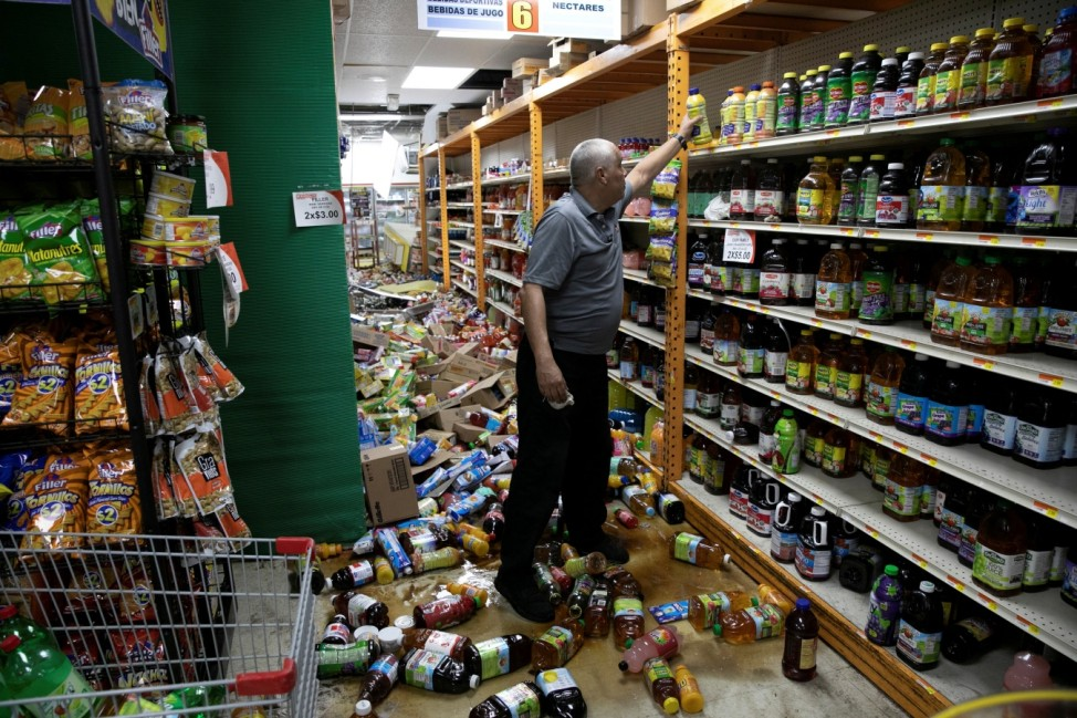 A worker cleans up a shop after an earthquake in Guanica