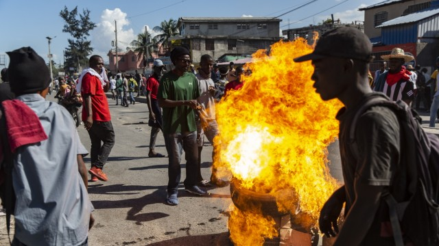 December 6, 2019, Port Au Prince, Haiti: Protesters light stacks of tires and garbage on fire to serve as roadblocks al