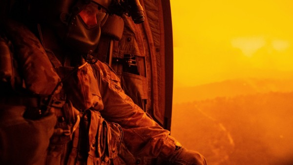 Warrant Officer Class Two Darrel Rowe, from the 5th Aviation Squadron, searches the ground from an Australian Army CH-47F Chinook during the flight to Omeo