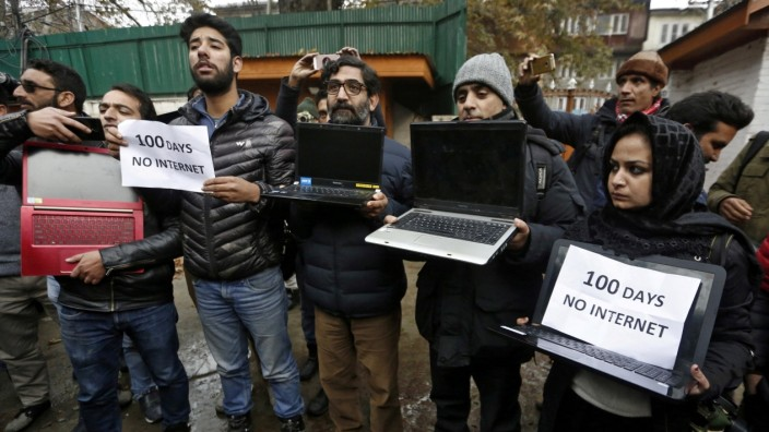 FILE PHOTO: Kashmiri journalists display laptops and placards during a protest demanding restoration of internet service, in Srinagar