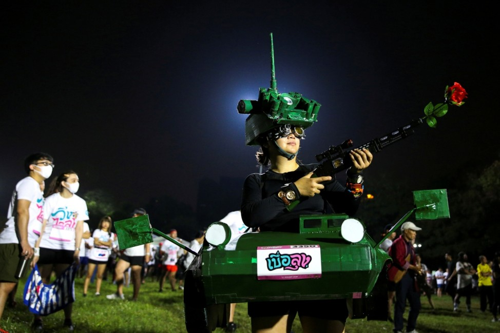 A runner dressed in a tank costume takes part in the 'Run Against Dictatorship' event at a public park in Bangkok