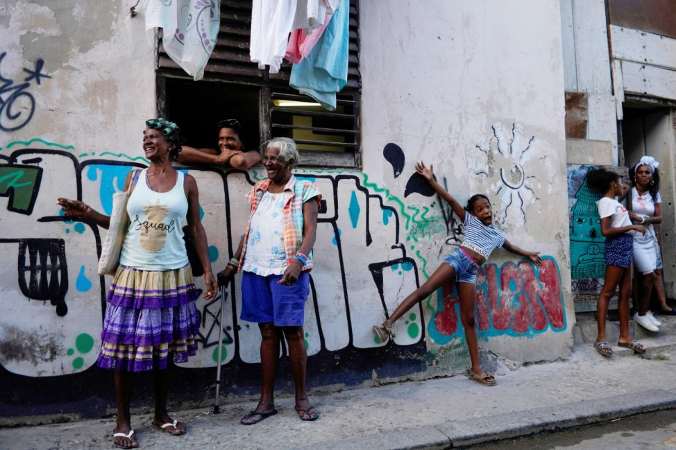 Unsichtbare Glücksbringer: Bewohner der kubanischen Hauptstadt Havanna freuen sich über Straßenmusiker (nicht im Bild).  Neighbors chat as they watch Cuban and New Orleans musicians after a parade in downtown Havana