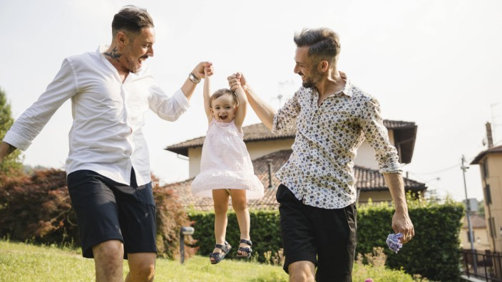 Happy gay couple playing with their child in the garden model released Symbolfoto property released