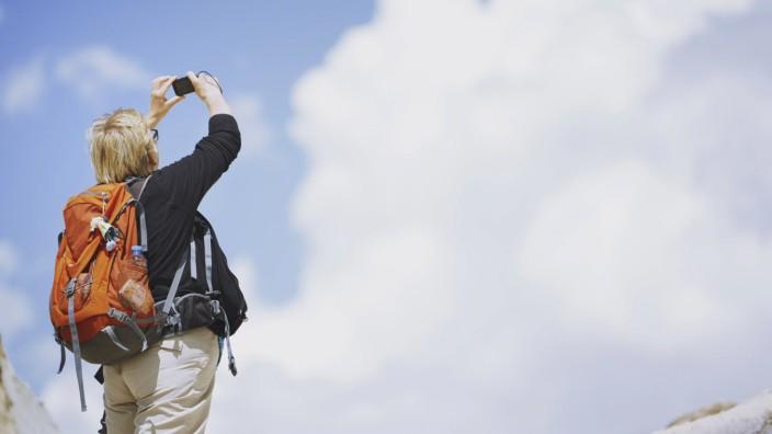Touristin mit Rucksack und Handy