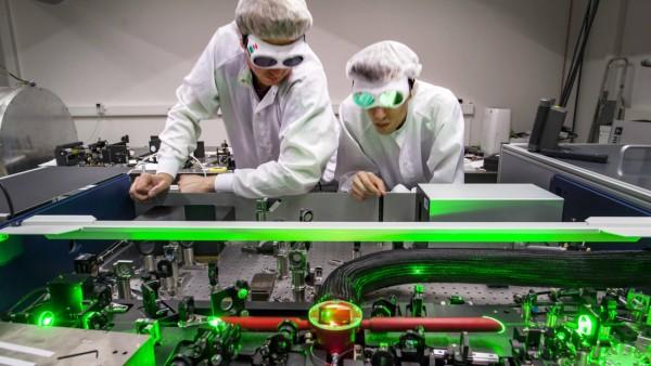 Doktoranden während ihrer Forschungsarbeit beim justieren ihres Versuchsaufbaus Laser Labor der Arb