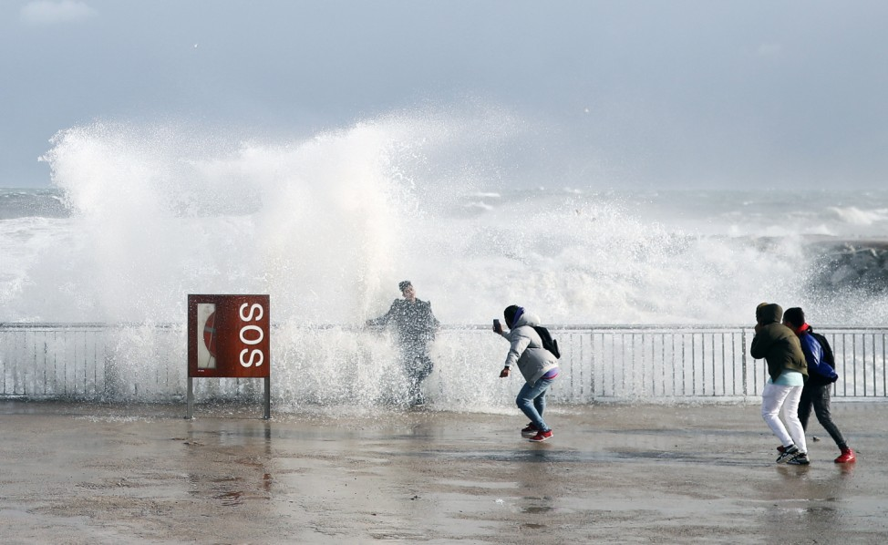 Tourists take a pictures as sea waves cover them during the storm 'Gloria' on Barceloneta beach, in Barcelona