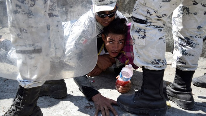 A member of Mexico's National Guard arrest a migrant, part of a caravan travelling to the U.S., near the border between Guatemala and Mexico, in Ciudad Hidalgo