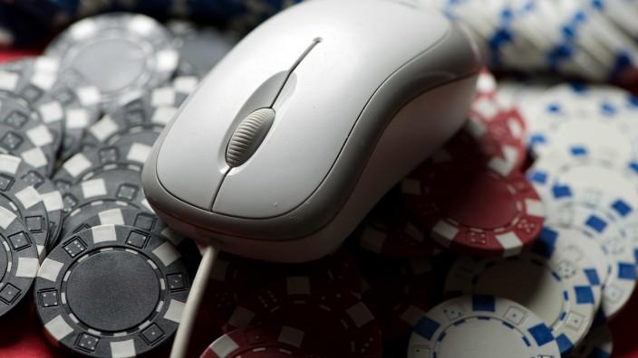 Online-Glücksspiel: Eine Computermaus liegt auf Poker-Chips