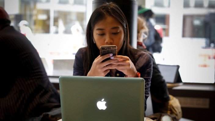 FILE PHOTO: A woman uses her Apple iPhone and laptop in a cafe in lower Manhattan in New York City