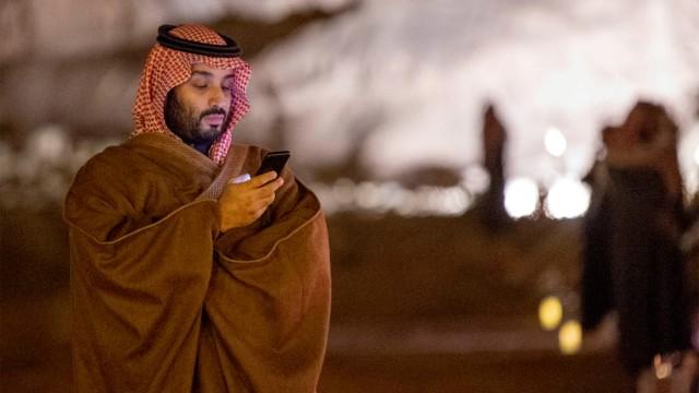 FILE PHOTO: Saudi Arabia's Crown Prince Mohammed bin Salman uses his phone during a meeting with Japan's Prime Minister Shinzo Abe in Riyadh