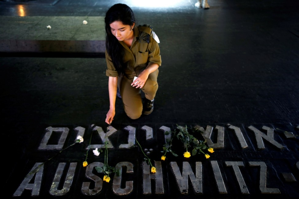 FILE PHOTO: An Israeli soldier places a flower next to the name of a former death camp as she visits the Hall of Remembrance at the Yad Vashem World Holocaust Remembrance Center, on the annual Israeli Holocaust Remembrance Day, in Jerusalem