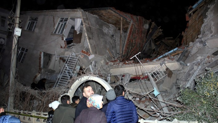 People stand outside a collapsed building after an earthquake in Elazig