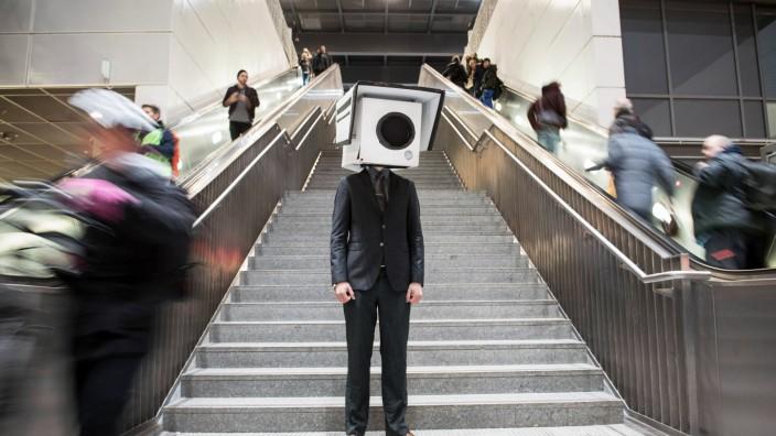 Ein Teilnehmer mit einer Maske in Form einer Überwachungskamera bei einer Aktion gegen gegen den Aus