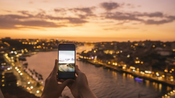 Woman s hands holding smartphone with a photo of panoramic view of Porto at sunset, Portugal model released Symbolfoto P