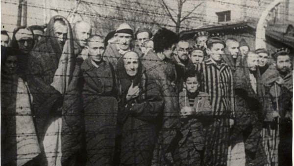FILE PHOTO: Holocaust survivors stand behind a barbed wire fence after the liberation of Nazi German death camp Auschwitz-Birkenau in 1945 in Nazi-occupied Poland, in this handout picture