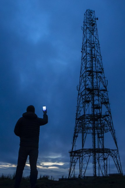 Huawei concerns A man holds a mobile phone near the Windy Hill Transmitter on Saddleworth Moor in South Pennines. Britai