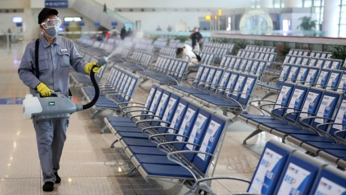 Workers in protective mask disinfects a waiting hall following the outbreak of a new coronavirus at the Nanjing Railway Station, in Nanjing, Jiangsu