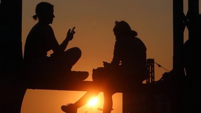 Sommerabend in München junge Frauen sitzen auf dem Geländer der Hackerbrücke und genießen den Sonne