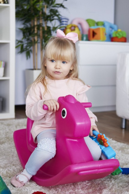 Portrait of little girl sitting on pink rocking horse in the living room model released Symbolfoto p