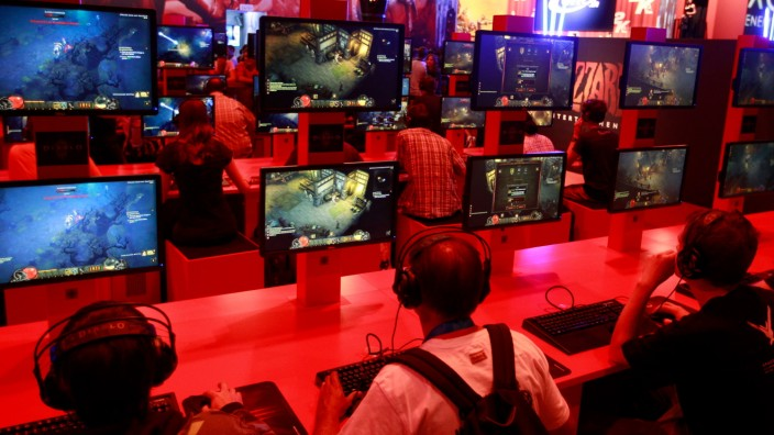 Visitors play 'Diablo' during the Gamescom 2012 fair in Cologne