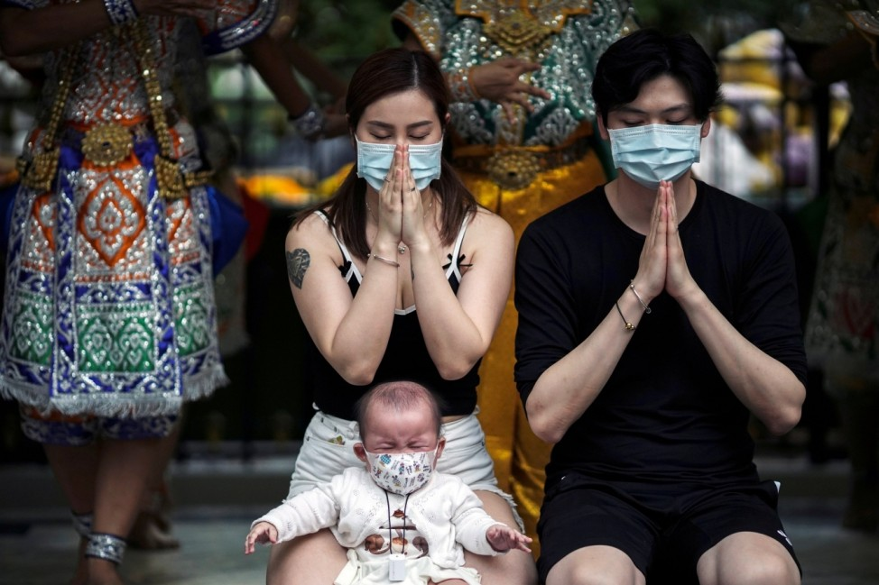 Chinese tourists wearing protective masks pray at the Erawan Shrine in Bangkok