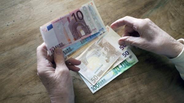 Geld: Seniorin hält Geldscheine in der Hand