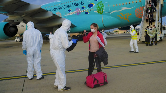 Reiseversicherung: Männer in Schutzanzügen empfangen am Flughafen Marseille eine Frau, die aus Wuhan kommt.