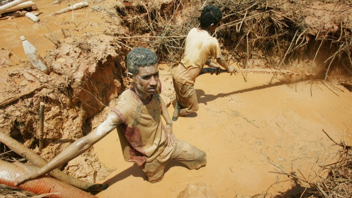 Unlicensed Venezuelan miner uses water jet to hose down earth as he hunts for gold near Las Cristinas concession