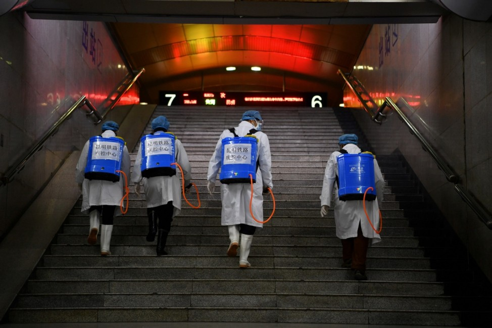 Workers with sanitizing equipment walk up a flight of stairs as they disinfect a railway station in Kunming
