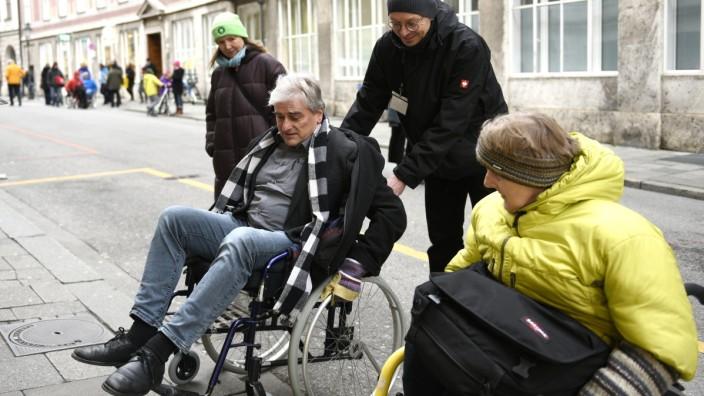 Paul Bickelbacher sitzt im Rollstuhl und testet gemeinsam mit einer weiteren Rollstuhlfahrerin, wie barrierefrei München ist. Die beiden versuchen, im Rollstuhl über einen Bordstein zu fahren.