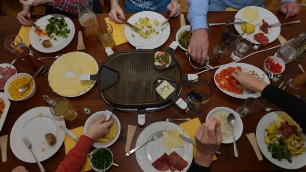 Ein voll beladener Esstisch, auf dem gerade Raclette gegessen wird.